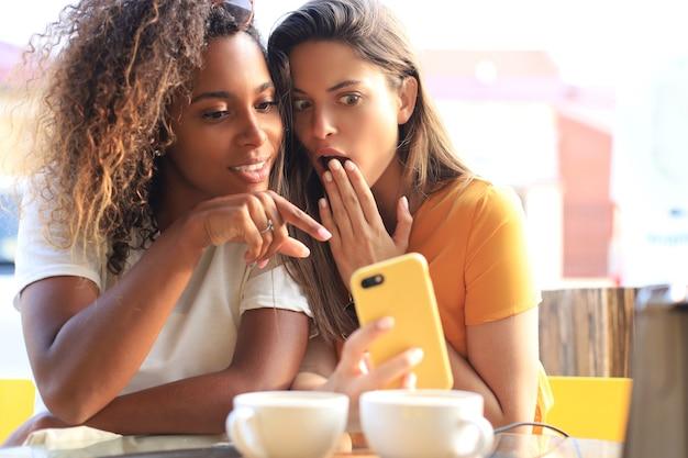 コーヒーを飲みながら携帯電話を見ているカフェに座っている2人の美しい若い女性。
