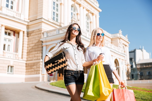 Две красивые молодые женщины гуляют по улице с сумками для покупок