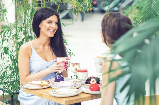Two beautiful young women are having coffee and desserts together at outdoors cafe.