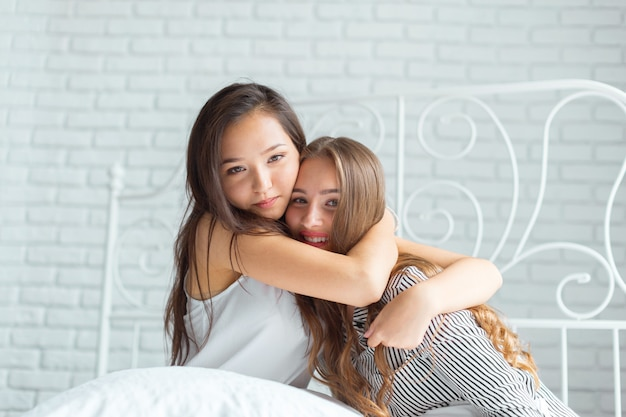 Two beautiful young women in bed pajamas party