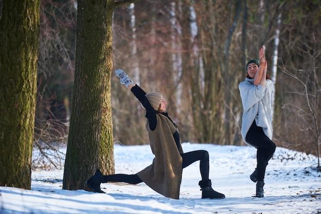 2 красивых молодой женщины делая йогу outdoors в парке зимы.