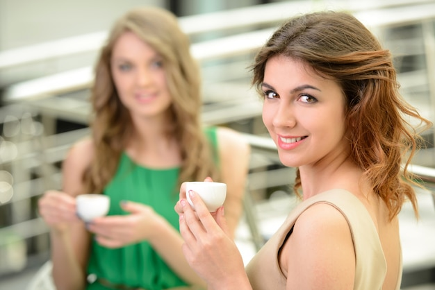 Two beautiful young women drinking coffee at the restaurant