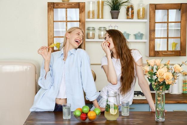 2人の美しい若い女性が台所で果物を食べる