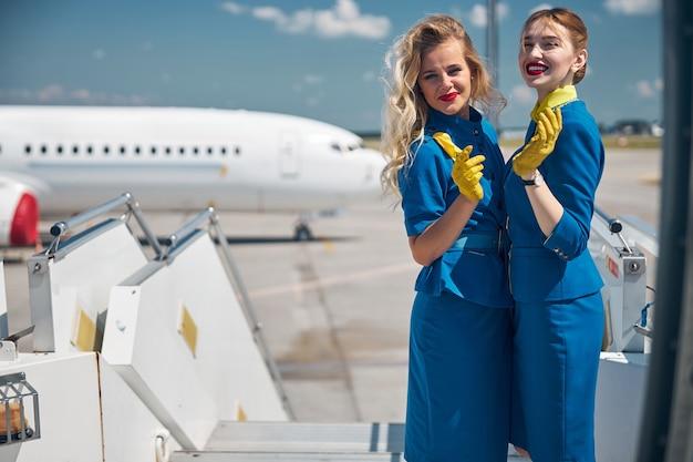 Две красивые молодые женщины-стюардессы в синей форме смотрят в камеру и улыбаются, стоя на лестнице самолета