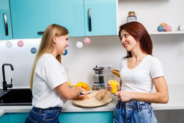 두 명의 아름다운 젊은 여성 친구가 집 식탁에 서서 빵을 먹고 오렌지 주스를 마신다