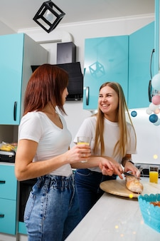 Two beautiful young women friends stand at the kitchen table at home and eat bread and drink orange juice