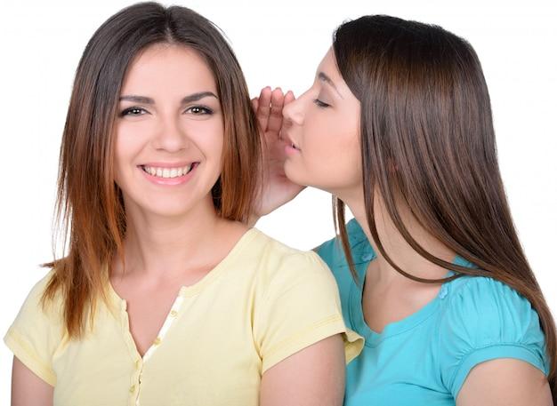 Two beautiful young women gossiping.