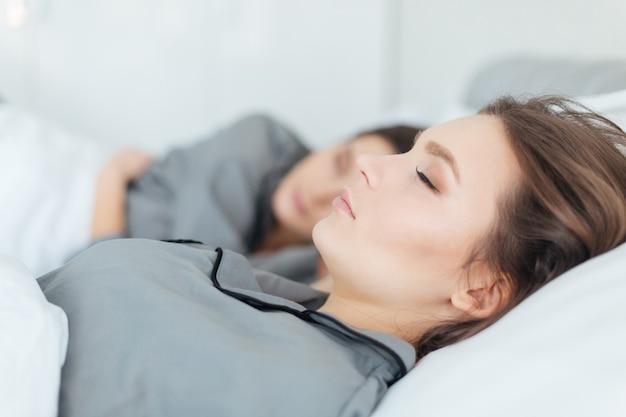 Two beautiful young women in grey pajamas sleeping in bed