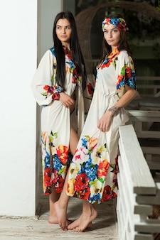 白いインテリアのビーチパレオで2人の美しい若い女性