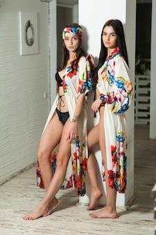 白いリゾートのインテリアのビーチパレオで2人の美しい若い女性