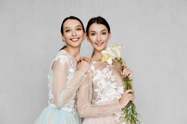 Две красивые молодые женщины в прозрачных платьях из тюля с кружевом позируют одинаково