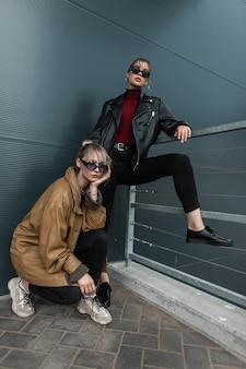 야외에서 금속 벽 근처에서 포즈를 취하는 선글라스에 가죽 재킷을 입은 세련된 데님 옷을 입은 두 명의 아름다운 젊은 여성