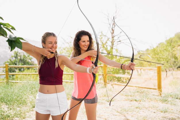 Two beautiful young women practicing archery in the field