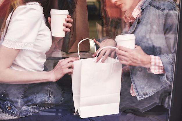 カフェに座ってコーヒーを飲みながら買い物の後、楽しい会話をする2人の美しい若い女性。