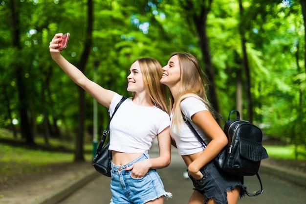 2人の美しい若い女性は、日当たりの良い公園で電話でselfieを取る。ガールフレンド。