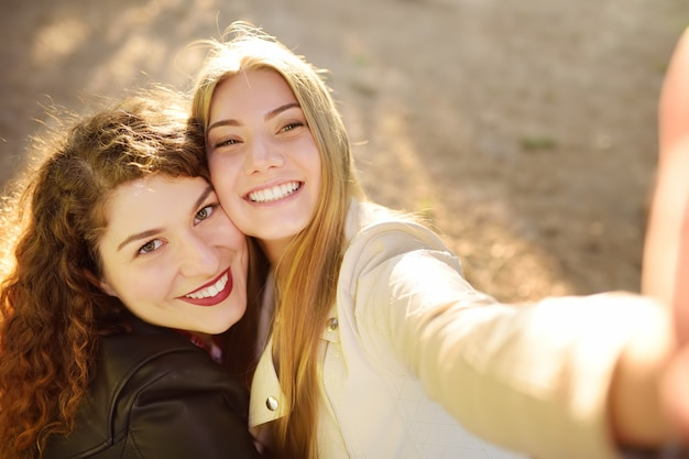 Two beautiful young women take selfie on sunny park. girlfriends.