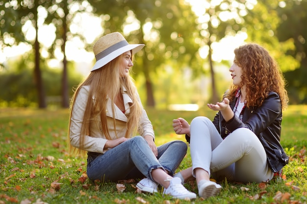 Two beautiful young women talking while sitting on the ground at sunny park.