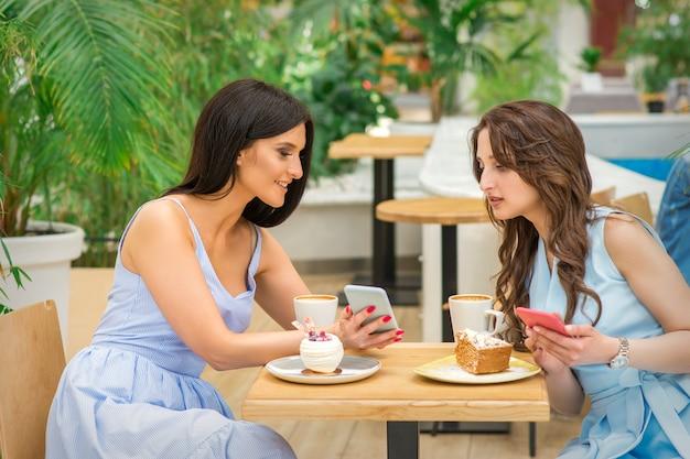 Две красивые молодые женщины вместе смотрят что-то по телефону за столиком в кафе