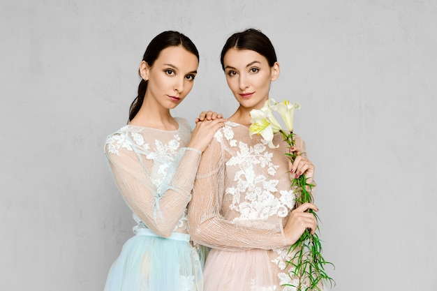 Two beautiful young women in transparent tulle dresses with lace posing in identical manner