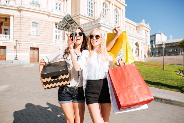 Two beautiful young women walking along the street together and holding shopping bags