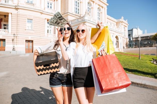 Две красивые молодые женщины вместе гуляют по улице и держат сумки с покупками