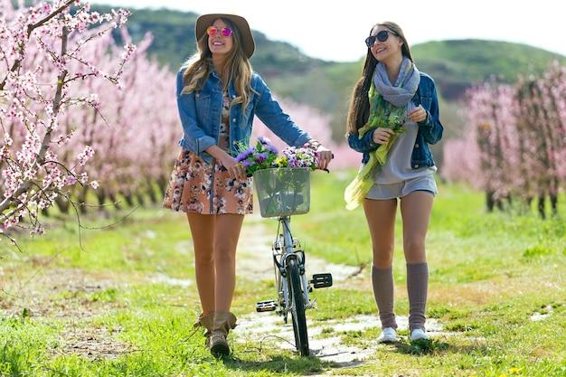 フィールドでヴィンテージバイクを持つ2人の美しい若い女性。