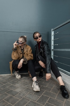 재킷, 안경, 지사미, 운동화를 신고 세련된 스트리트웨어를 입은 아름다운 두 자매가 금속 어두운 벽 근처에 앉아 있습니다