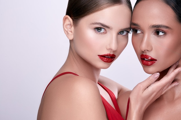 Two beauty faces with red lipstick, handsome women on grey background