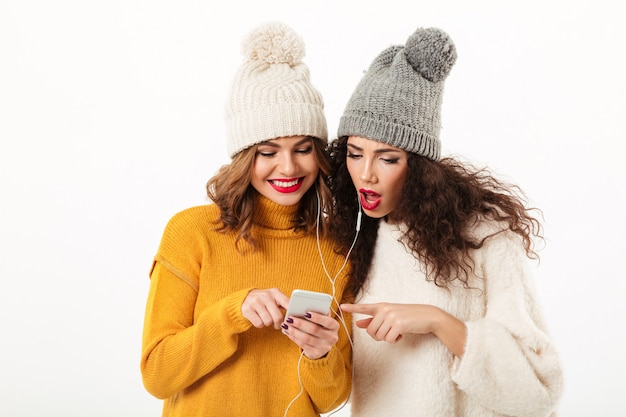 Two beauty girls in sweaters and hats standing together while using smartphone over white wall