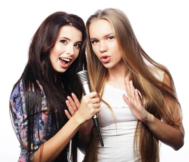 Две девушки-хипстеры красоты с микрофоном поют и веселятся