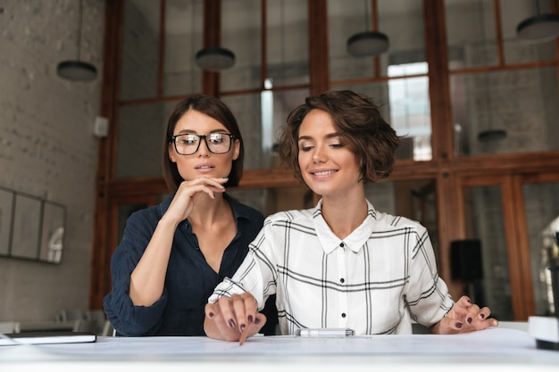 Two beauty pretty smiling women sitting by the table