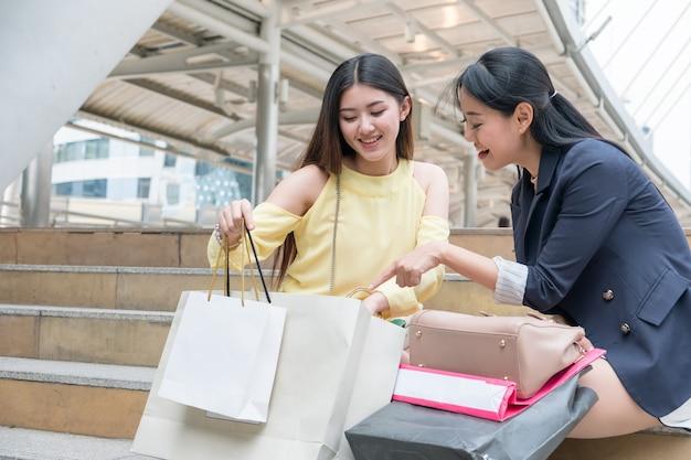2 つの美しさの女性が座って、買い物の紙袋を見て、見せる
