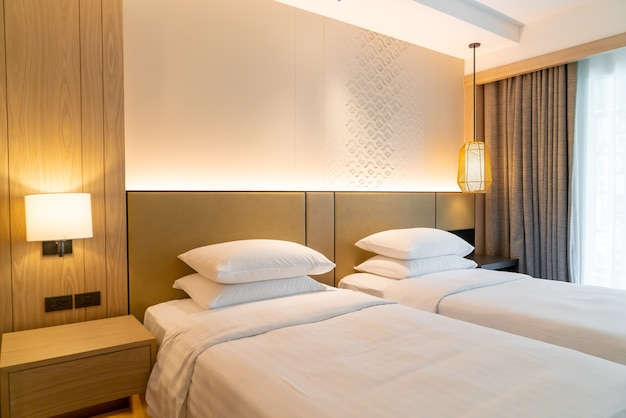 Two beds with pillows in hotel resort bedroom