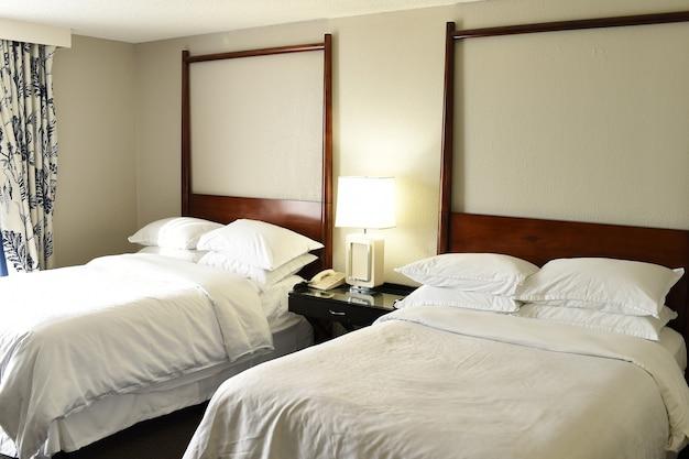 호텔이나 모텔 객실 또는 램프가 있고 아무도 없는 침실에 흰색 린넨과 베개가 있는 침대 2개