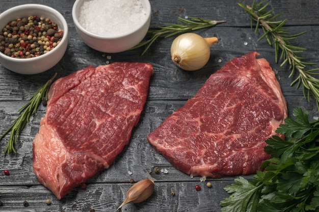 Два стейка из говядины, лук и розмарин на деревянном столе. кусочки свежего мяса.