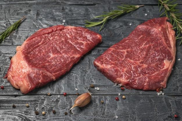木製のテーブルに2つのビーフステーキ、ローズマリーとニンニク。新鮮な肉のかけら。