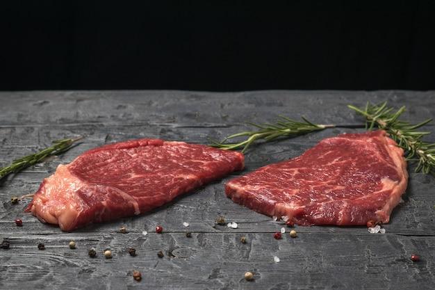 Два стейка из говядины с зеленью на черном деревянном столе. кусочки свежего мяса.