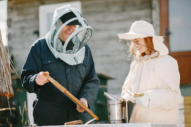 養蜂場で働く2人の養蜂家。つなぎ服での作業。
