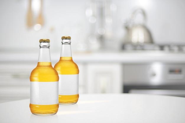 長い首と台所のテーブルに空白のラベルが付いた2つのビール瓶。モックアップデザインプレゼンテーション