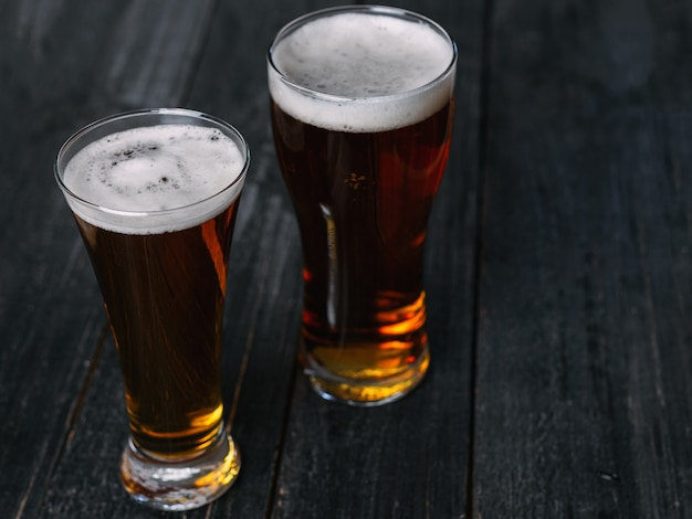 Two beers on a dark wooden table