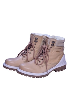 Two beige winter boots with laces stand toes first on a white clipping background.