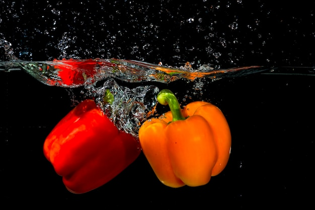 Two bell pepper falling into the water on black background