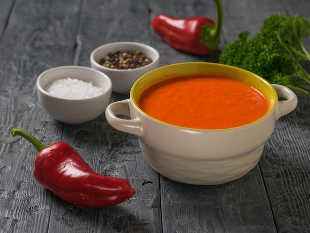木製のテーブルにクリームスープと調味料を入れた2つのピーマン。菜食のスープ。