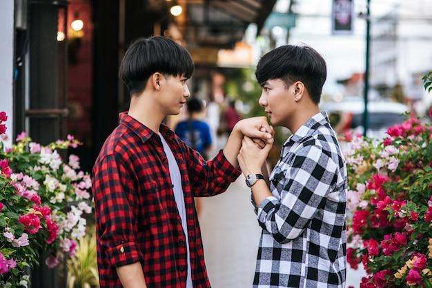 シャツを着て縁石の上に立っている2人の最愛の若者。