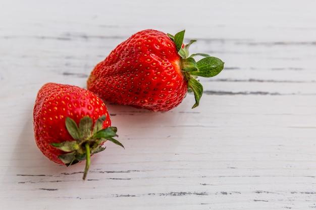 Две ягоды красной спелой клубники на светлом деревянном фоне. сезонные витамины. крупный план. вид сверху. пространство для текста.