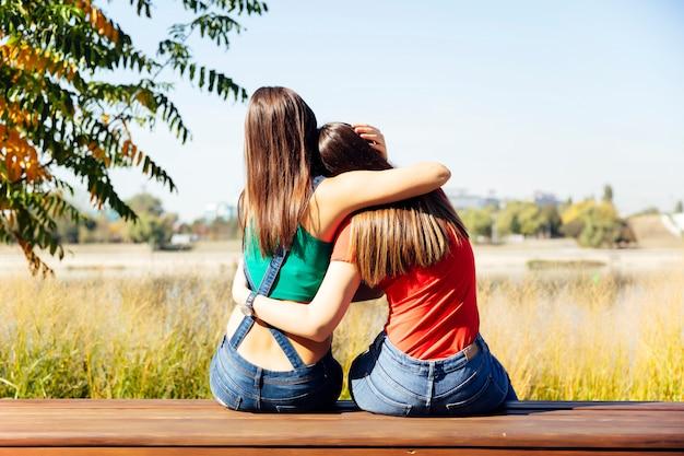 Две лучшие подруги обнимаются вместе