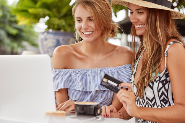 Two best female friends have fun together, make online shopping with laptop computer, use plastic credit card, pay for online purchase, look for special sales offers, enjoy coffee at restaurant