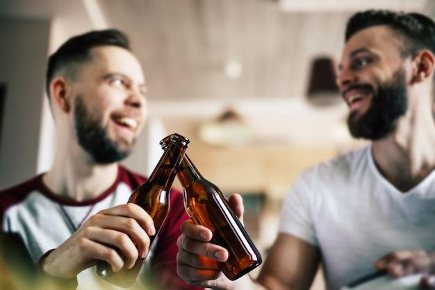 ソファでチームを応援しながら、テレビでスポーツの試合を観戦し、ビールを飲み、軽食を食べる2人の親友とサッカーファン