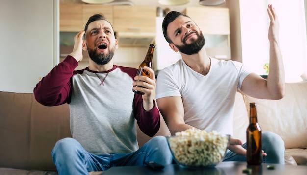 두 명의 가장 친한 친구와 축구 팬이 tv에서 스포츠 경기를보고, 맥주를 마시고, 소파에서 팀을 응원하면서 간식을 먹습니다.