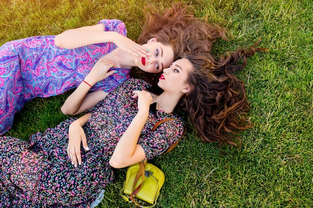 Two best friends in colorful boho dress and curly hair laying on the green grass